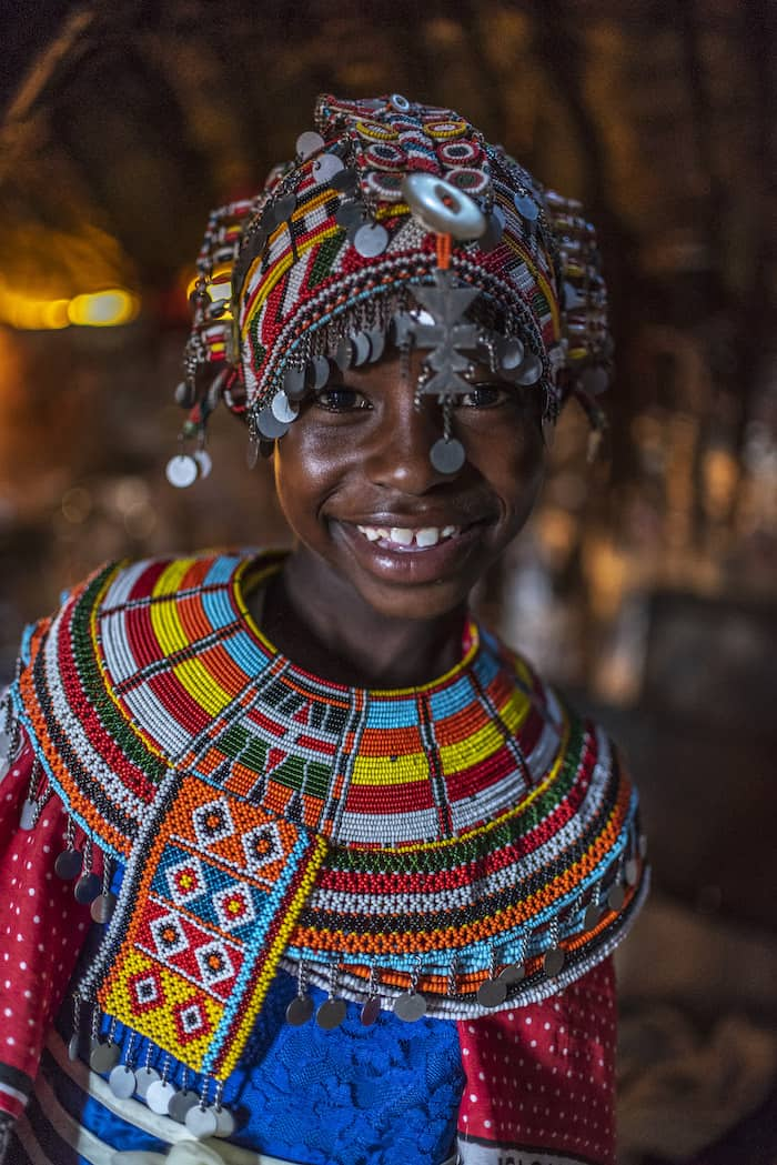 A girl wears an ornate beaded headdress with silver coins and an ornate beaded necklace and smiles at the camera.