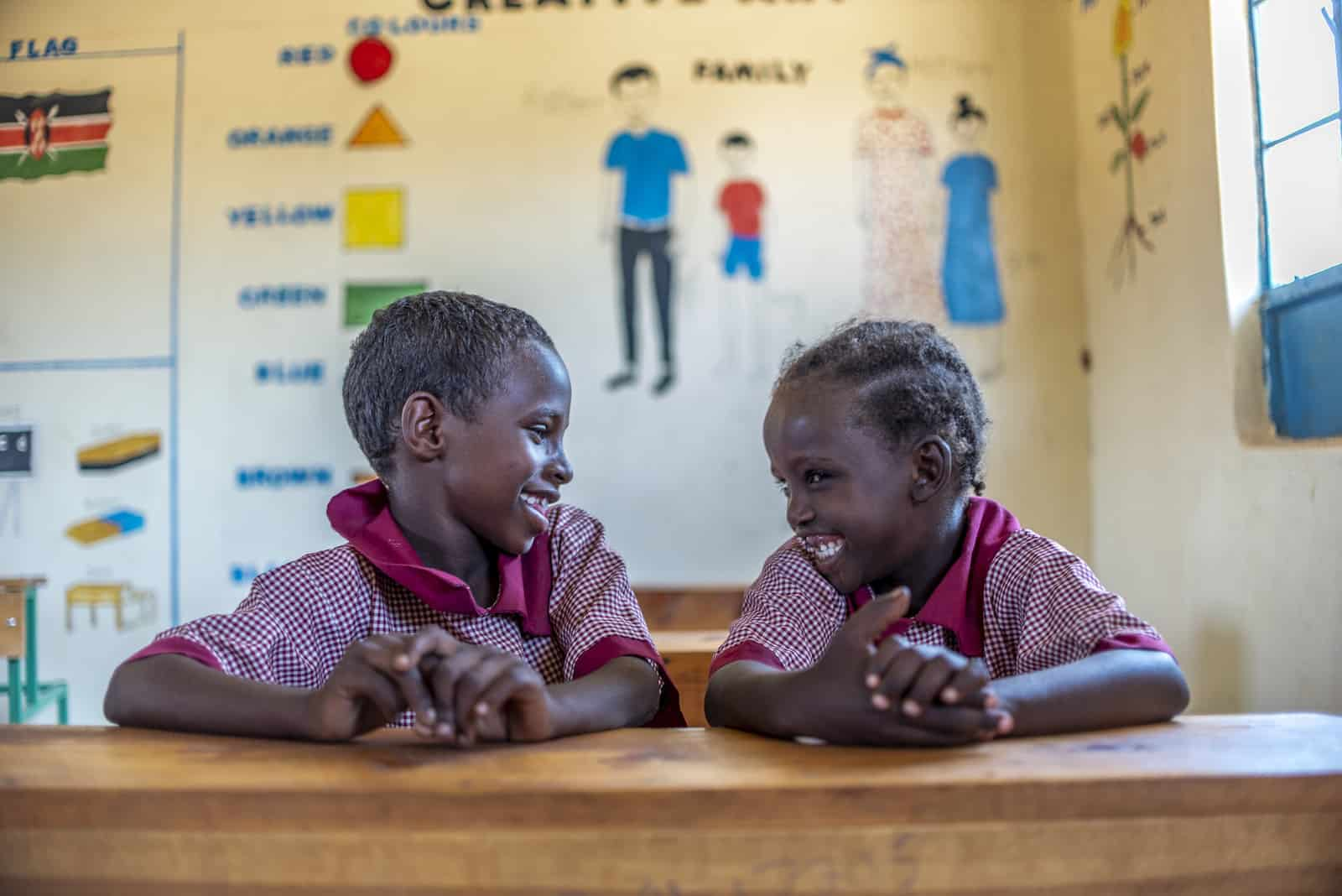 Two young girls where red checked school uniforms sit at a desk in a classroom and smile at each other.