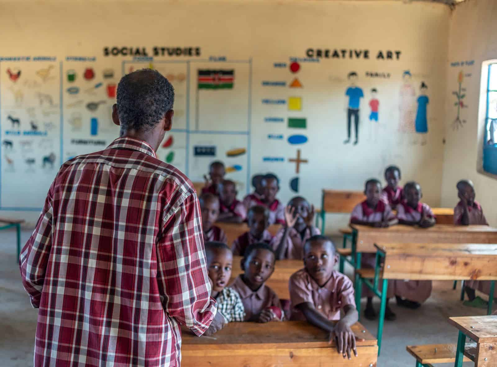 A man in a plaid shirt stands at the front of a classroom, with children wearing red school uniforms sitting at desks and listening.