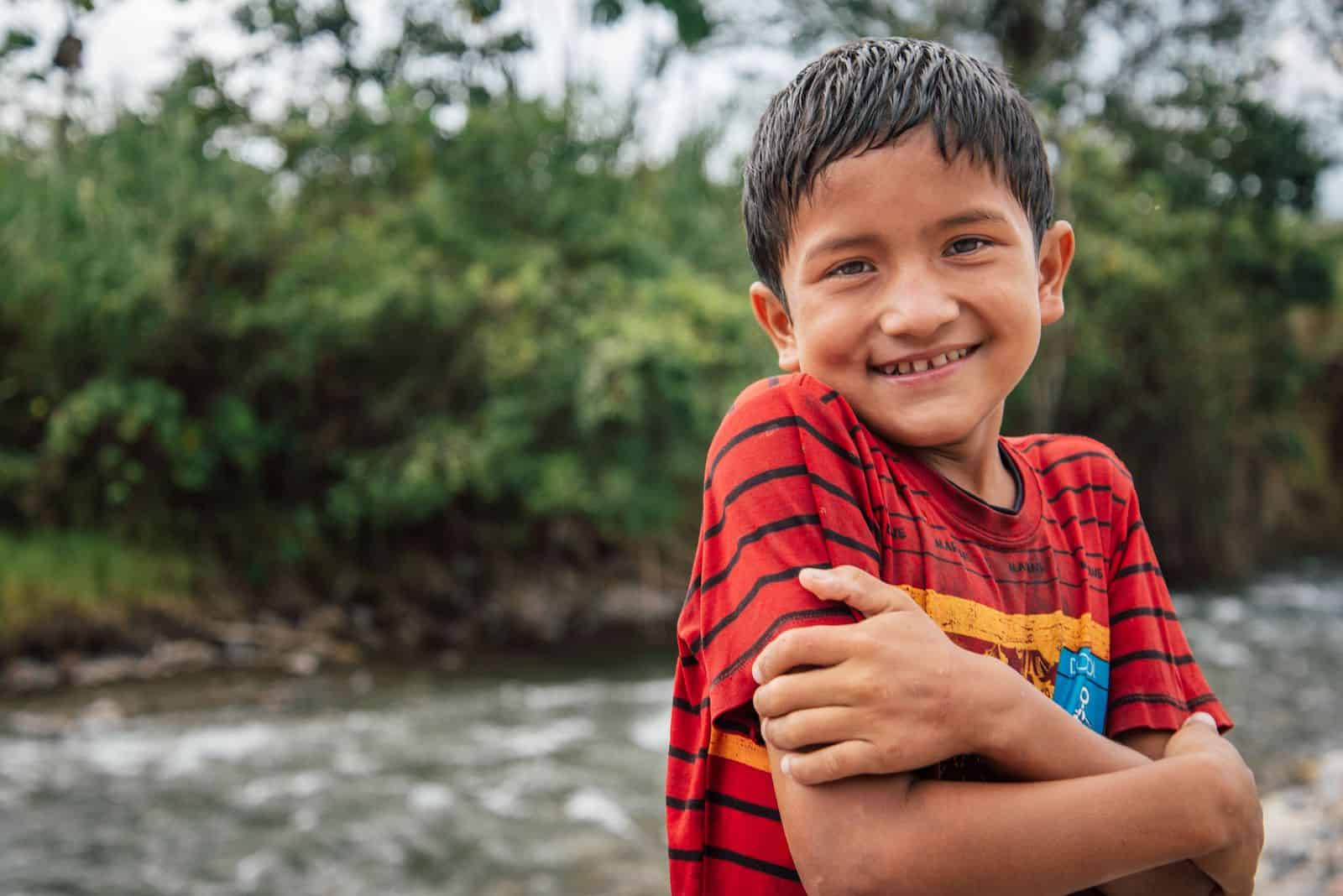 A boy in a red shirt hugs his arms across his chest and smiles. He is standing in front of a river in the Amazon jungle.