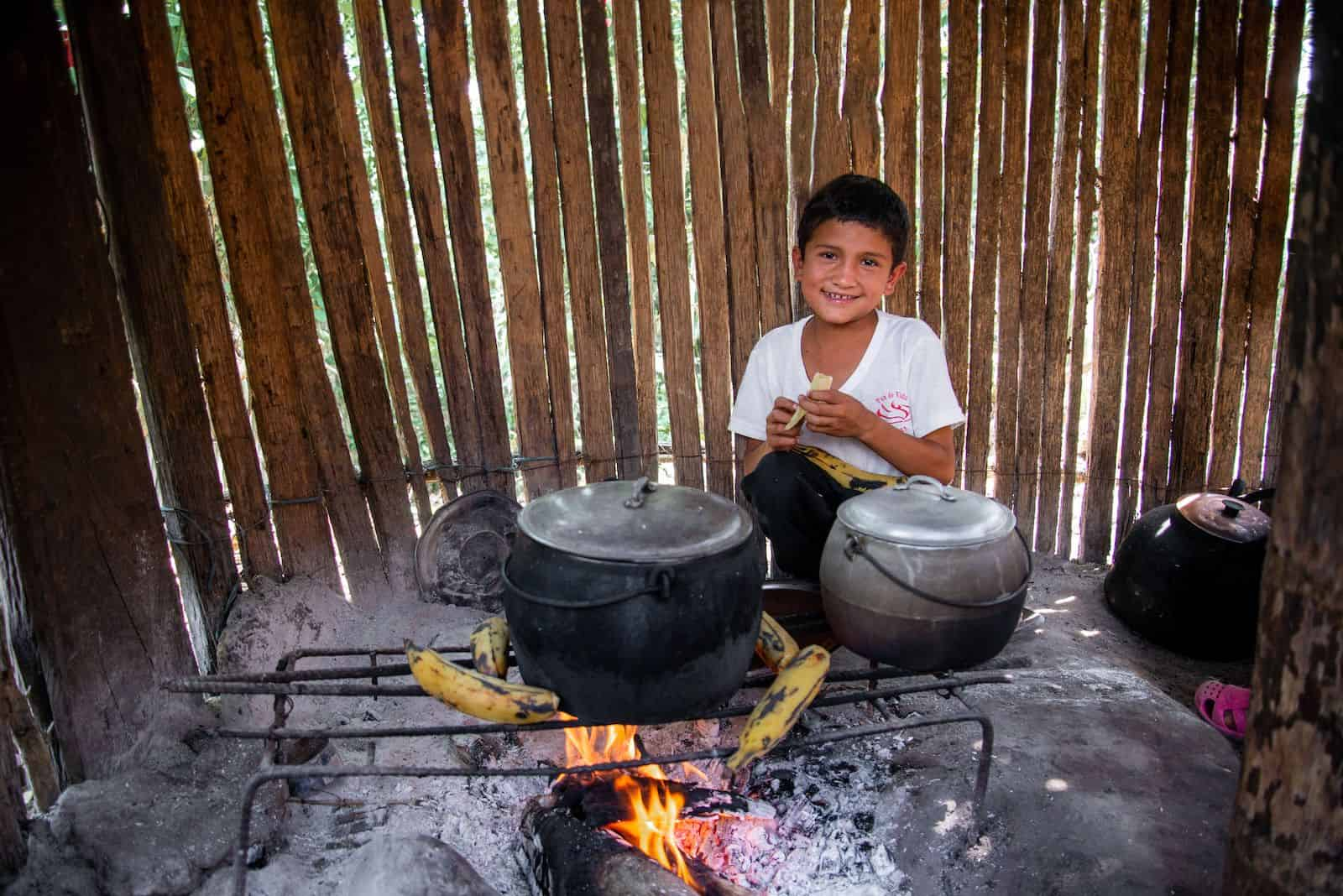 A boy wearing a white shirt crouches in front of a wood fire that has a wire frame over it with several plantains on it and two black pots.