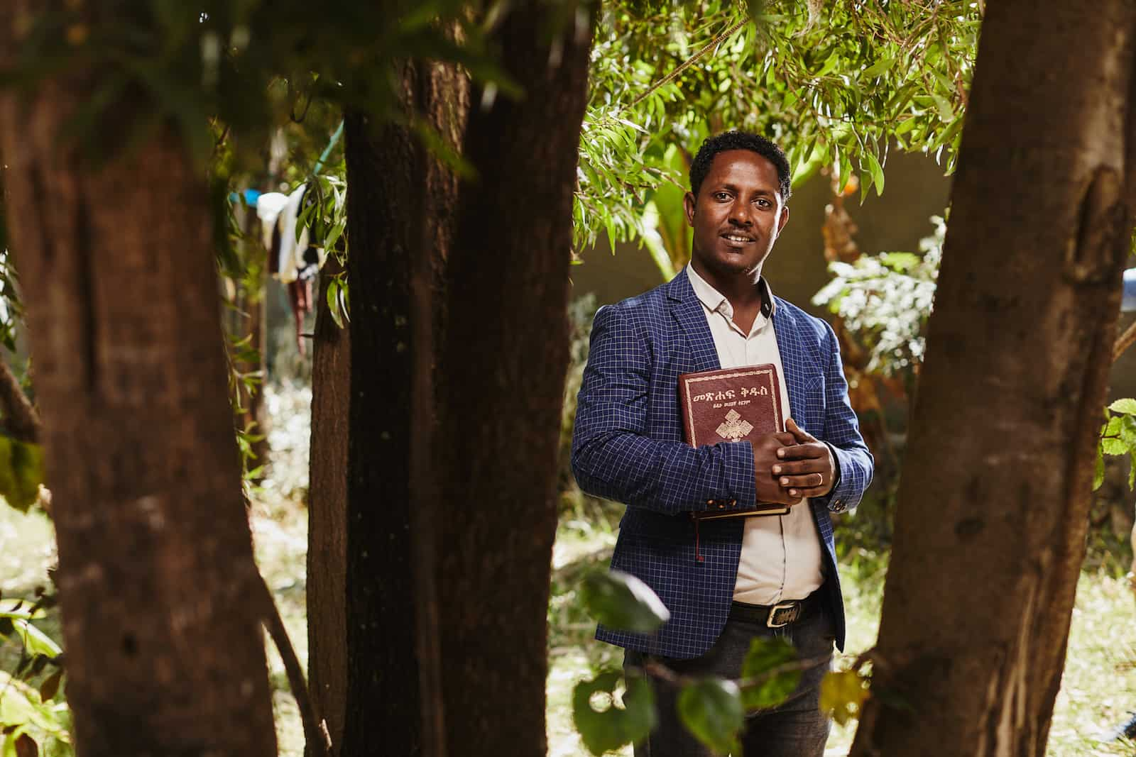 A man stands in a group of trees wearing a suit, holding a Bible and smiling into the camera.
