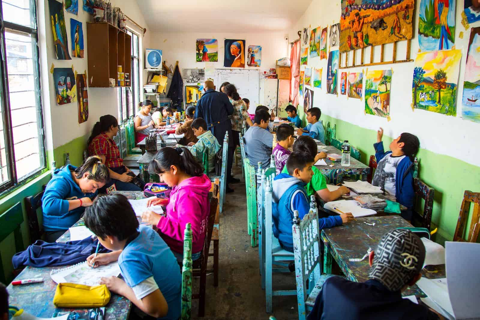 In a classroom full of brightly colored chairs and tables, children paint on white paper. The walls of the classroom are covered in paintings.