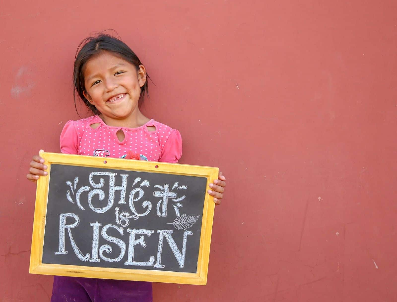 "A girl missing her front tooth smiles, holding a chalkboard that says, ""He is risen."" She is wearing a pink shirt and purple pants and stands in front of a coral colored wall."