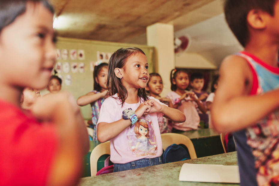 A young girl in the Philippines in a pink shirt makes a heart shape with her hands in front of her, singing and looking to the front of the class. She is in a classroom surrounding by kids doing the same thing.