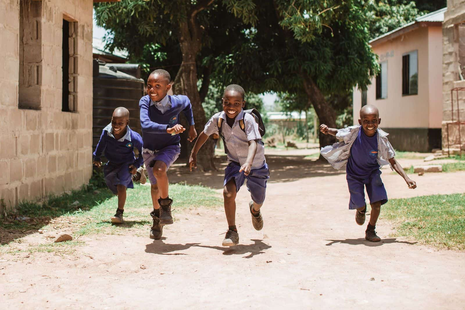 Four boys in Tanzania wearing purple school uniforms run towards the camera, smiling, down a dirt road.