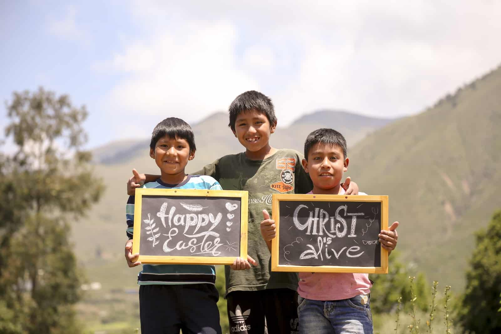 Three boys stand in front of green hills in Bolivia. The one on the left holds a sign that says, Happy Easter. The one on the right holds a sign that says, Christ is alive.