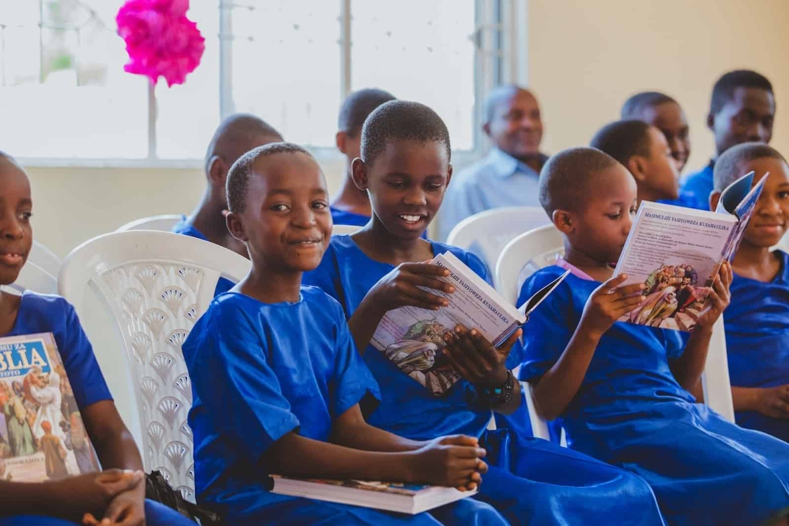 A group of girls in Tanzania wearing blue uniform dresses sit on white plastic chairs, each holding and reading Bibles. The girl in the foreground smiles at the camera.