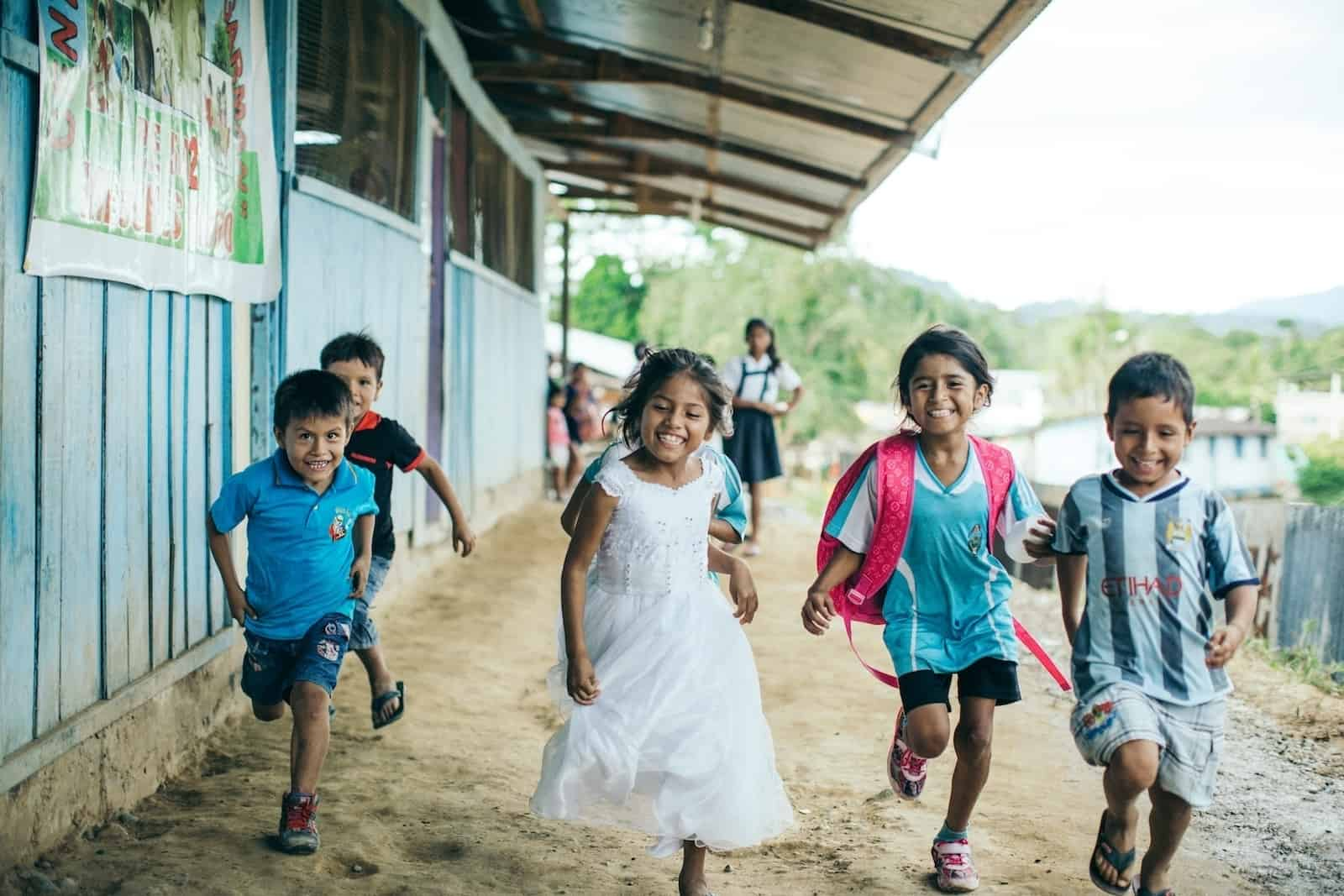 A group of children run down a path in Peru, next to a row of blue classrooms.