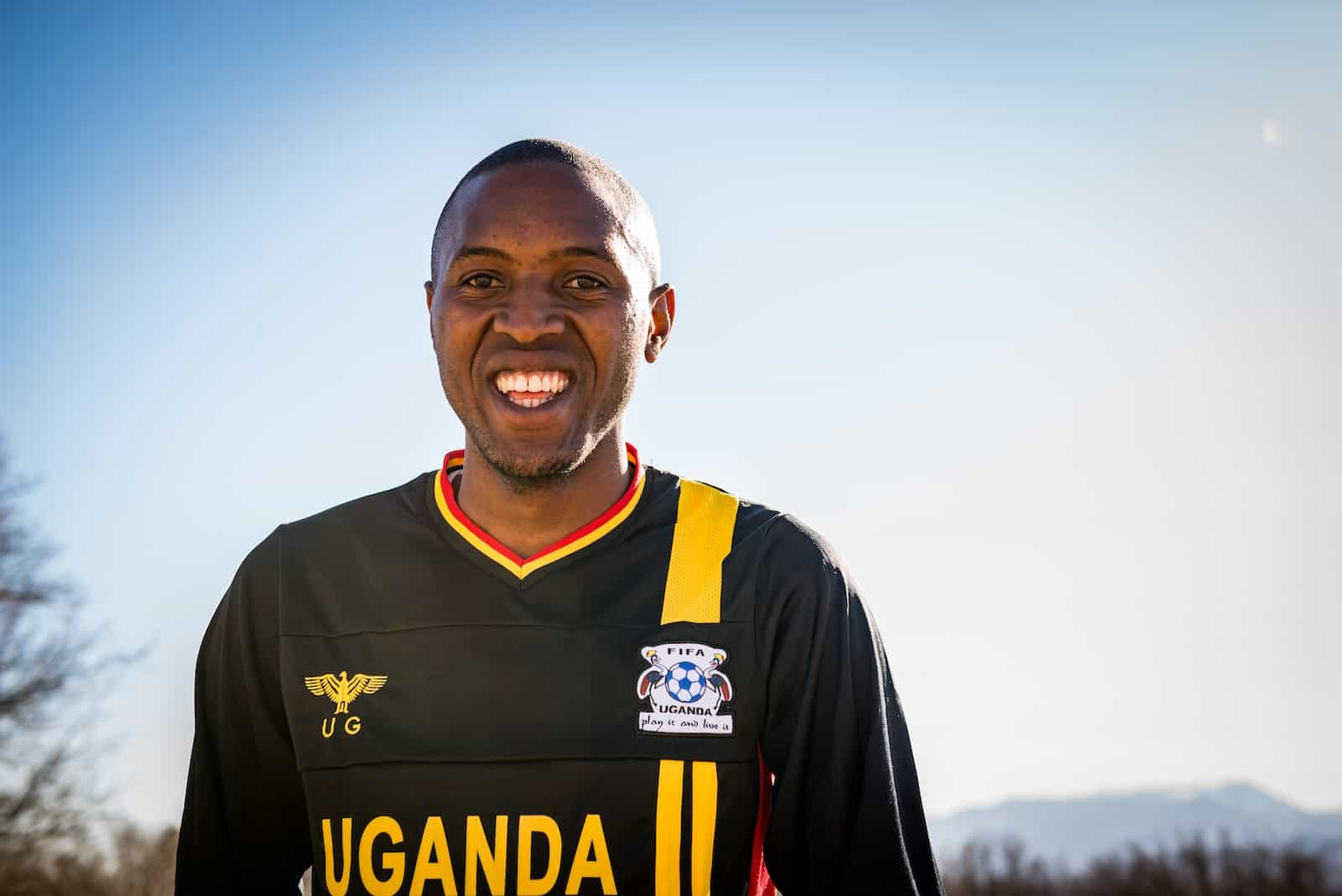 "A man smiles, wearing a black shirt that says, ""Uganda."""
