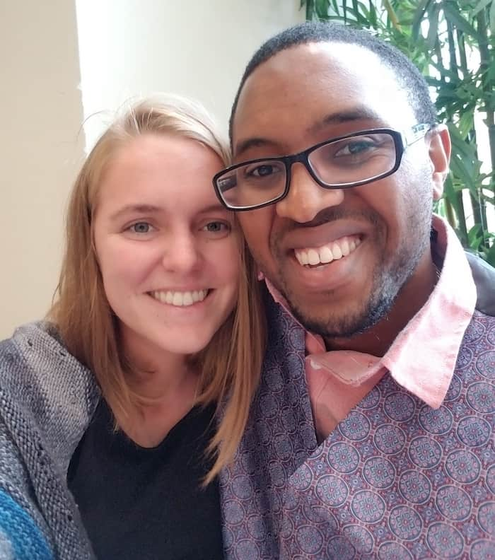 A woman with blonde hair wearing a black shirt and grey sweater smiles at the camera next to a man in glasses wearing a pink button-up shirt and grey vest.
