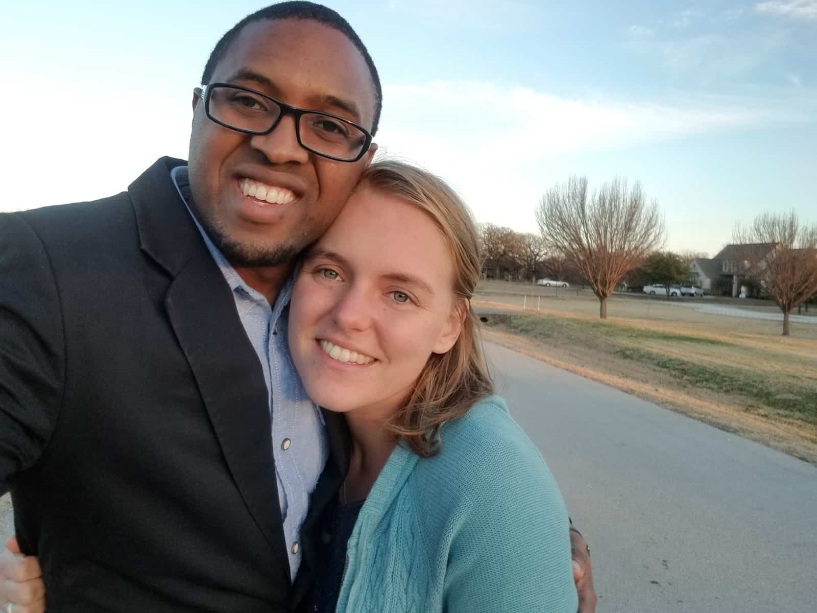 A man in a black suit coat and glasses smiles with his arm around a woman with blonde hair wearing a green sweater.