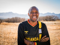 A man wearing a black jersey that says Uganda crosses his arms and smiles. He stands outside with trees and mountains in the distance.