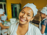 A young woman wearing a white chef's hat, white shirt and apron smiles at the camera, standing in a bakery.
