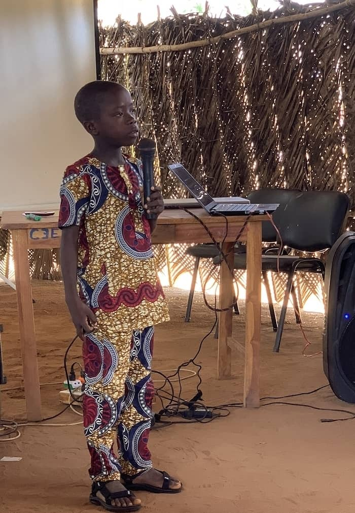 A boy in a patterned yellow and red Togolese outfit stands, speaking into a microphone. He is in a room made from woven leaves. He is an example of the Easter message of hope.