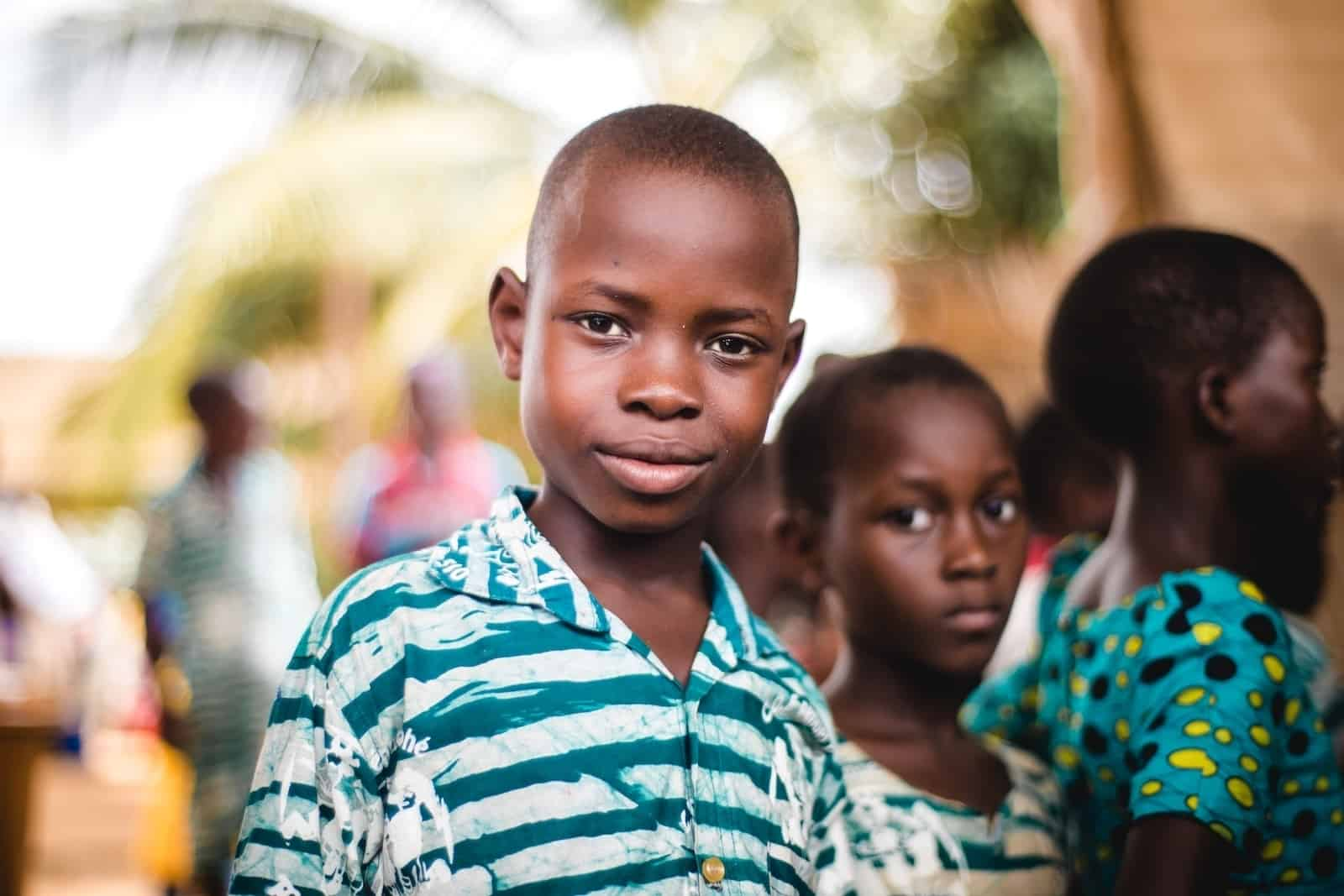 A boy from Togo wearing a green and white shirt looks into the camera. He is surrounded by children wearing similar colors. They stand outside with palm trees in the background.