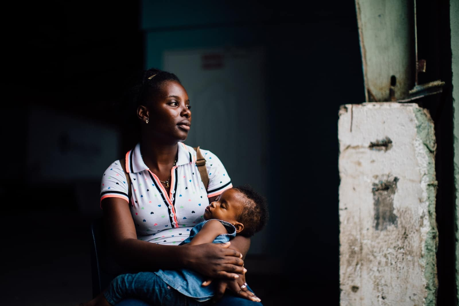 A woman in a white shirt sits in a dark room, looking out the window. She is holding a sleeping child in her lap.