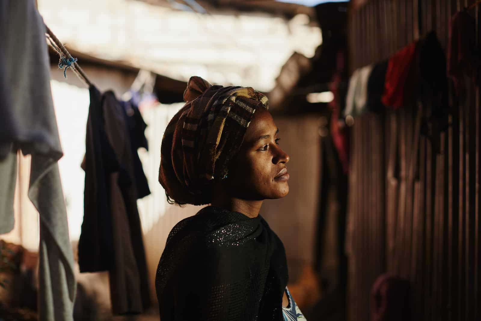 A woman wearing a plaid headscarf and black shawl looks to the side. She stands in a dark alley with laundry hanging on the line.