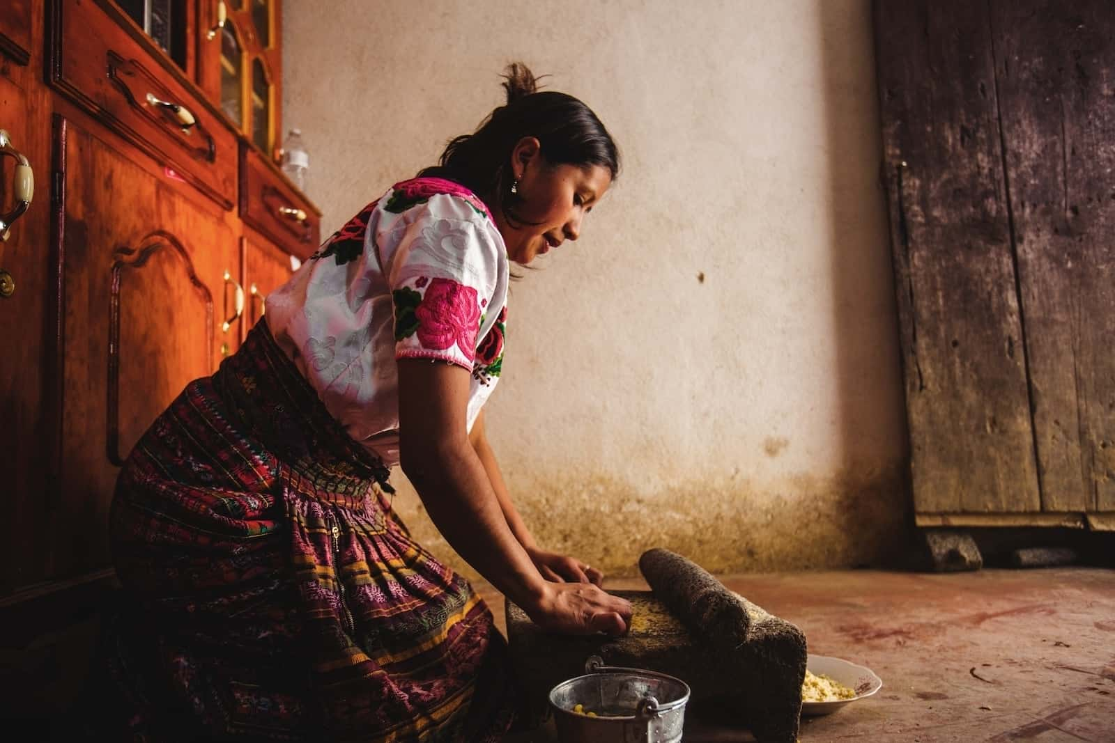 A woman wearing a colorful skirt with a pink and white shirt kneels in a room, grinding corn on a stone.