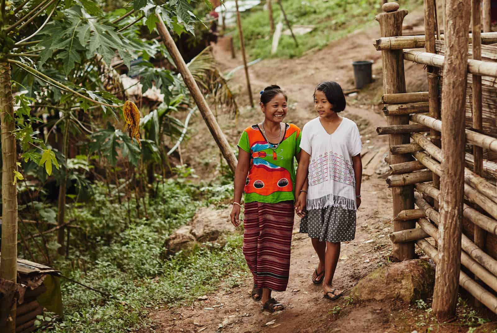 A woman wearing a patterned skirt and red and green shirt walks down a dirt path with a girl in a white shirt and grey skirt by her side. They are next to a bamboo home and forest.