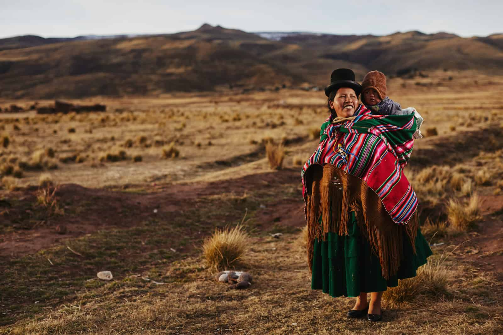 A woman wearing a black bowler hat, colorful shawl and traditional Bolivian clothes stands in a wide field, carrying a baby on her back.