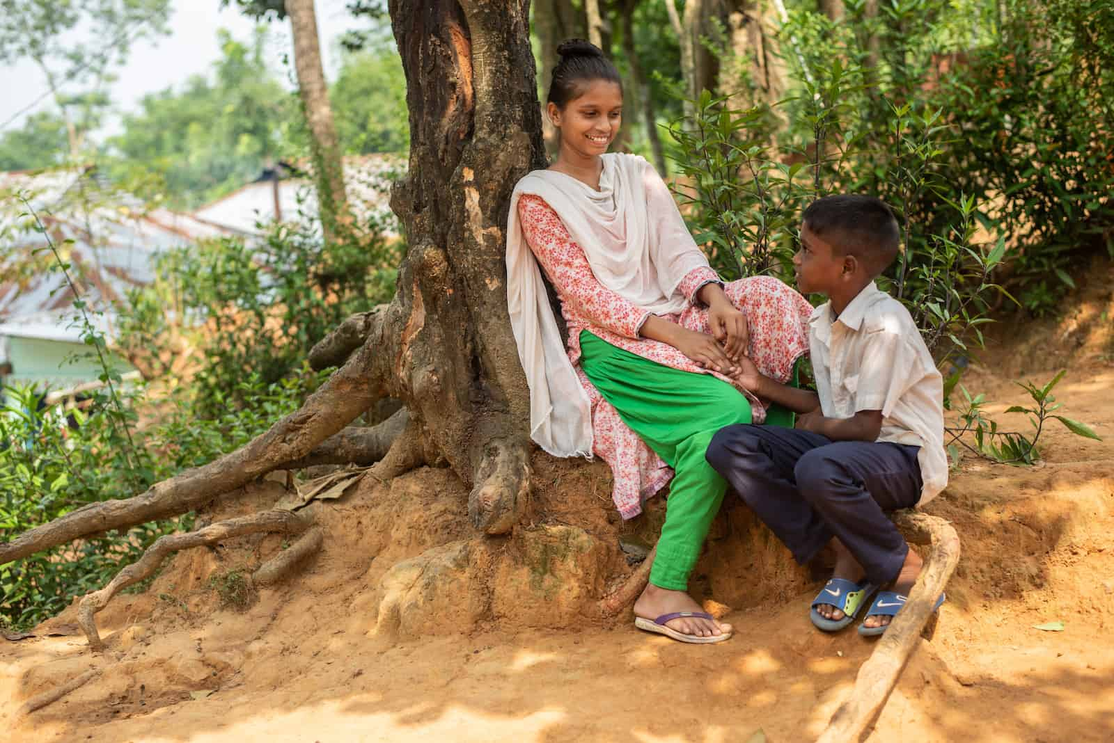 A girl wearing green pants, a pink shirt and a white scarf leans against the trunk of a large tree. A young boy wearing jeans and a white button-up shirt kneels below her as they smile at each other.