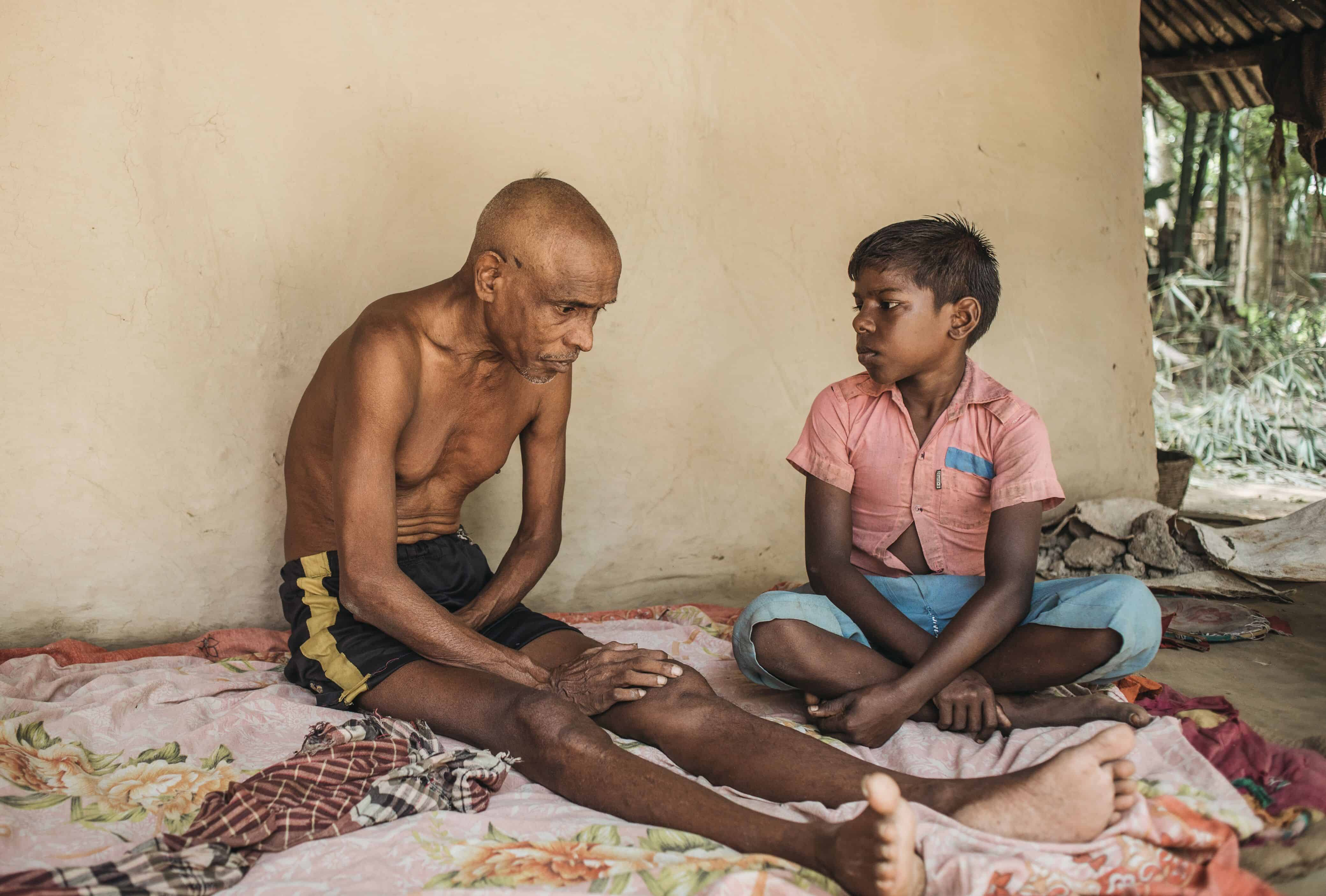 An older man without a shirt sits on a blanket against a tan colored wall, looking down at the ground. A young boy in a pink shirt sitting next to him looks at him.