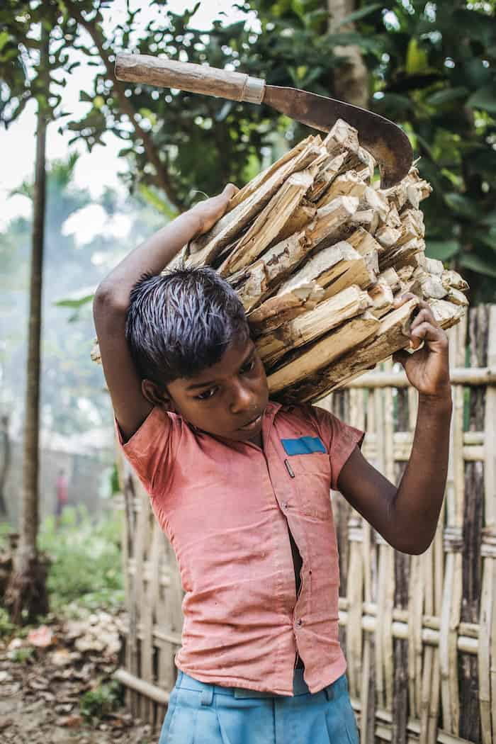 A 10-year-old boy wearing a coral-colored shirt carries a large bundle of wood on his shoulder, with a machete stuck in the top of the wood.