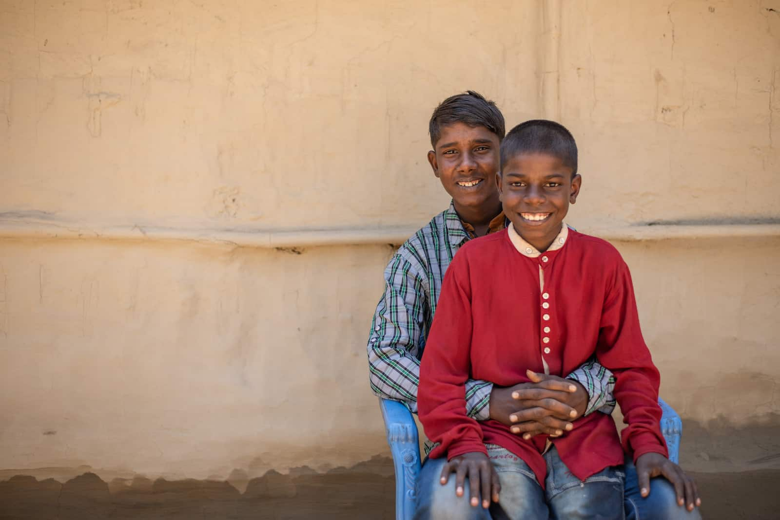 A young smiling boy wearing a red shirt sits in the lap of a smiling teenager wearing a blue plaid shirt, with his hands clasped around his brother.