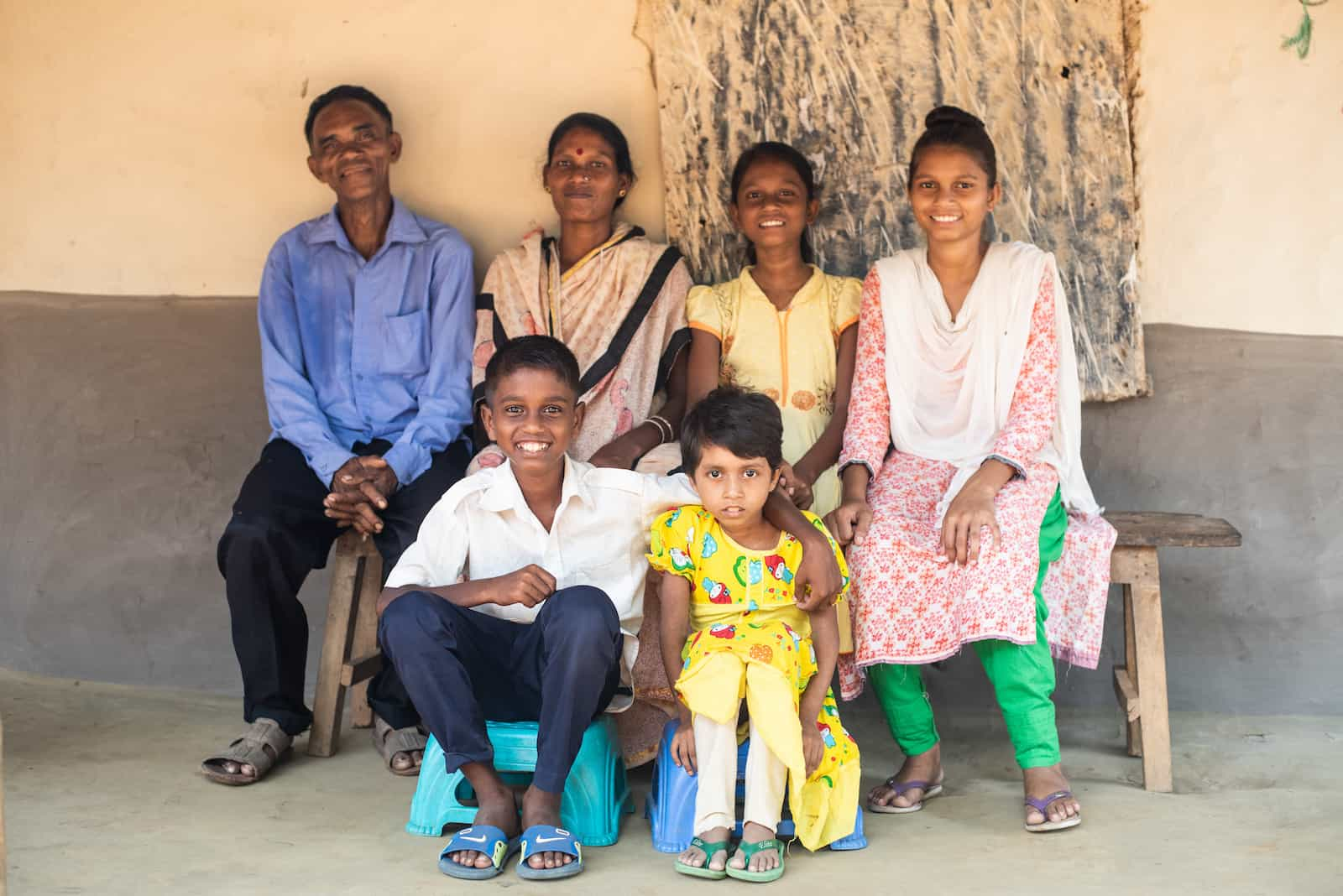 A family of six sits outside, smiling, including an older man in blue, a woman wearing a tan sari, a girl in a yellow dress, and another girl in a pink and green outfit. Below them are a young boy in a white shirt and blue pants and a young girl in a yellow dress.