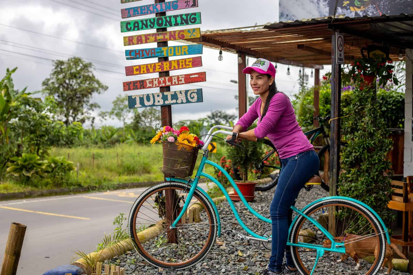 "A woman in a pink shirt, jeans and a baseball cap sits on a turquoise bike on a roadside, with a sign behind her that reads, ""Trekking, Canyoning, Rafting, Tubing,"" etc."