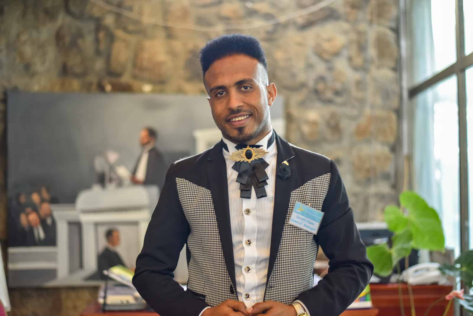 A man stands in a hotel lobby wearing a black, white and gray suit.