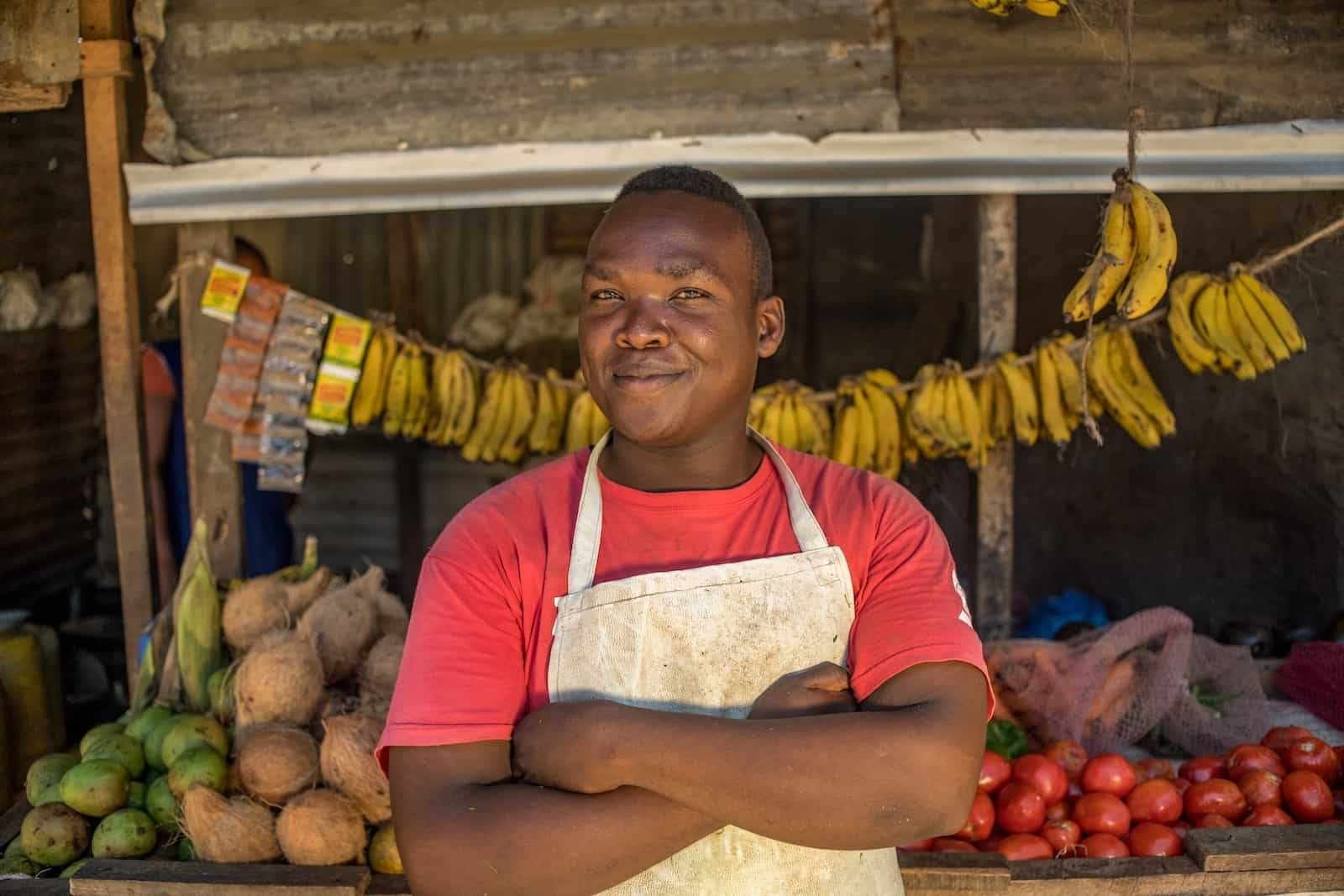 A Compassion graduate wearing a red T-shirt and white apron stands with his arms crossed, in front of a grocery stall, full of bananas, apples and coconuts.