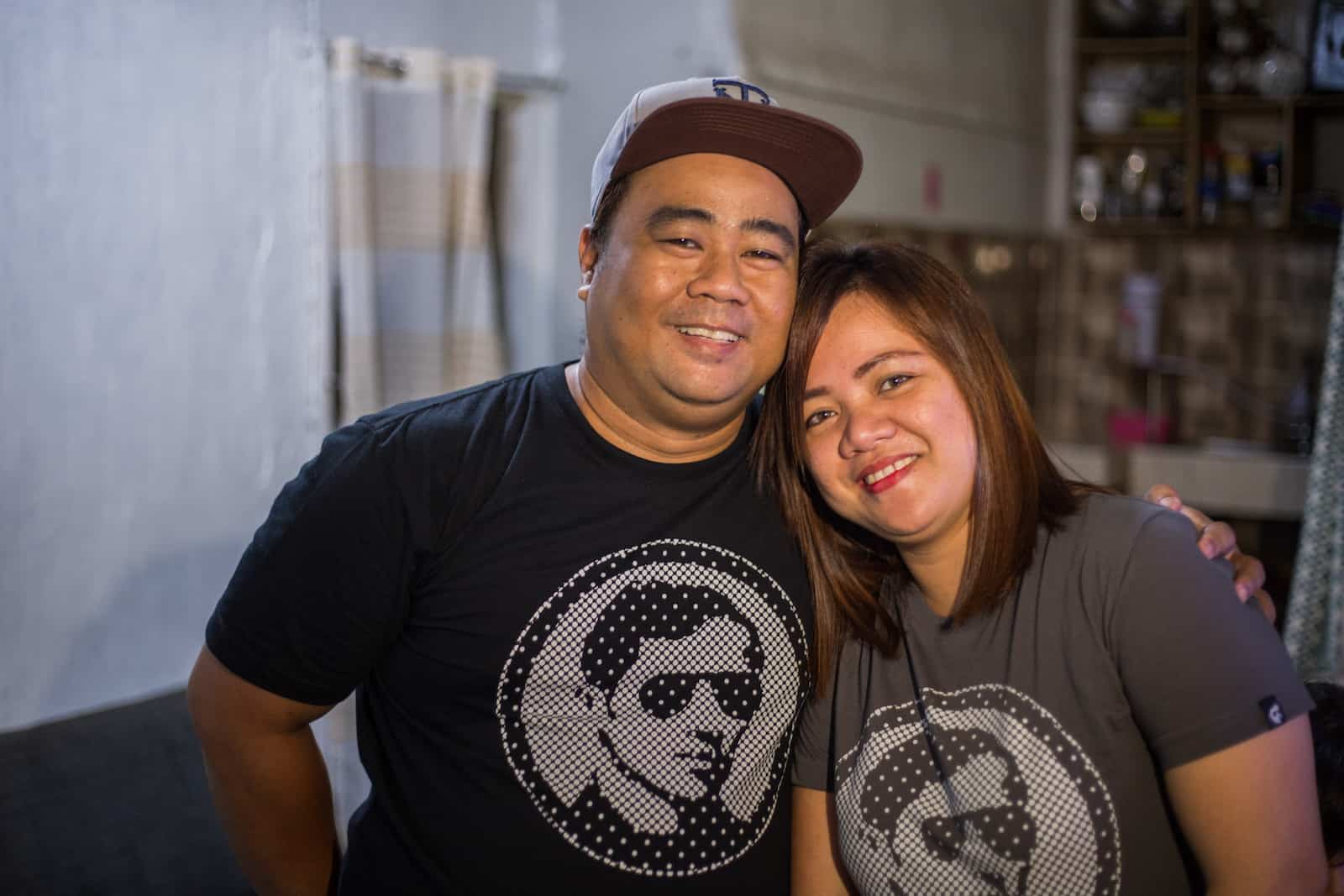 A man and a woman wearing matching black and grey T-shirts smile at the camera, the man's arm around the woman.