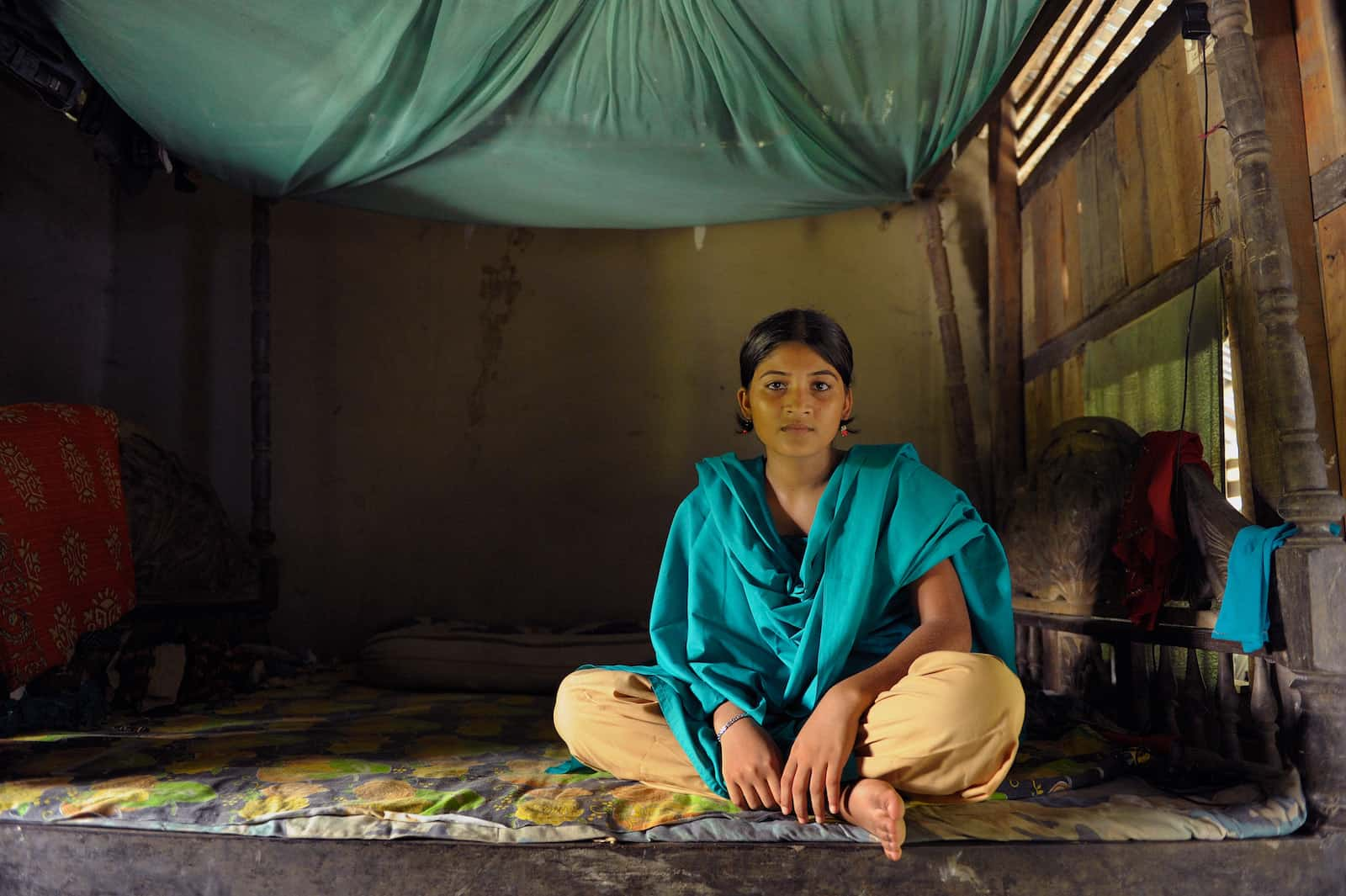 A girl in yellow pants and a green scarf sits on a woodframe bed with a mat on top and with a mosquito net above.