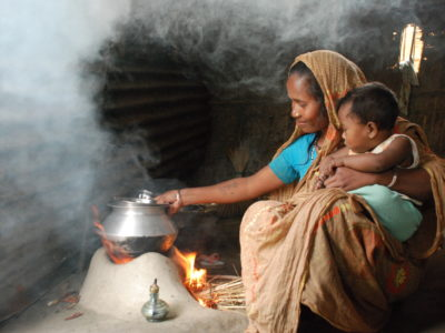 A woman with a baby in her lap sits inside in front of a small fire with a pot on top of it, with smoke in the air.