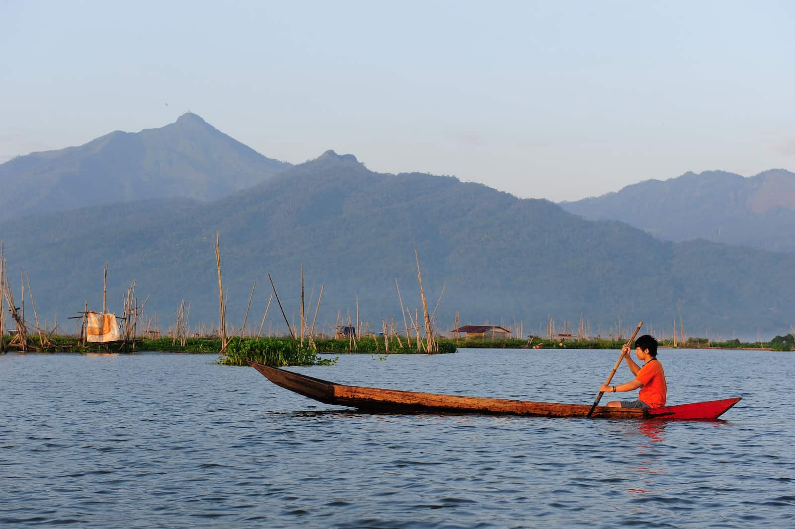 A young man in a red shirt sits in a long canoe, rowing on a large body of water, with mountains in the background.