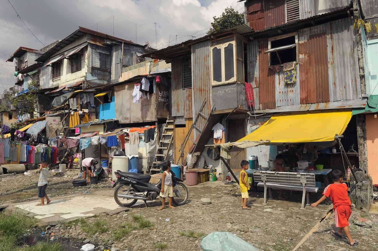 A row of makeshift homes on a street, several stories high, made from metal sheets and wood, showing poverty in Asia.