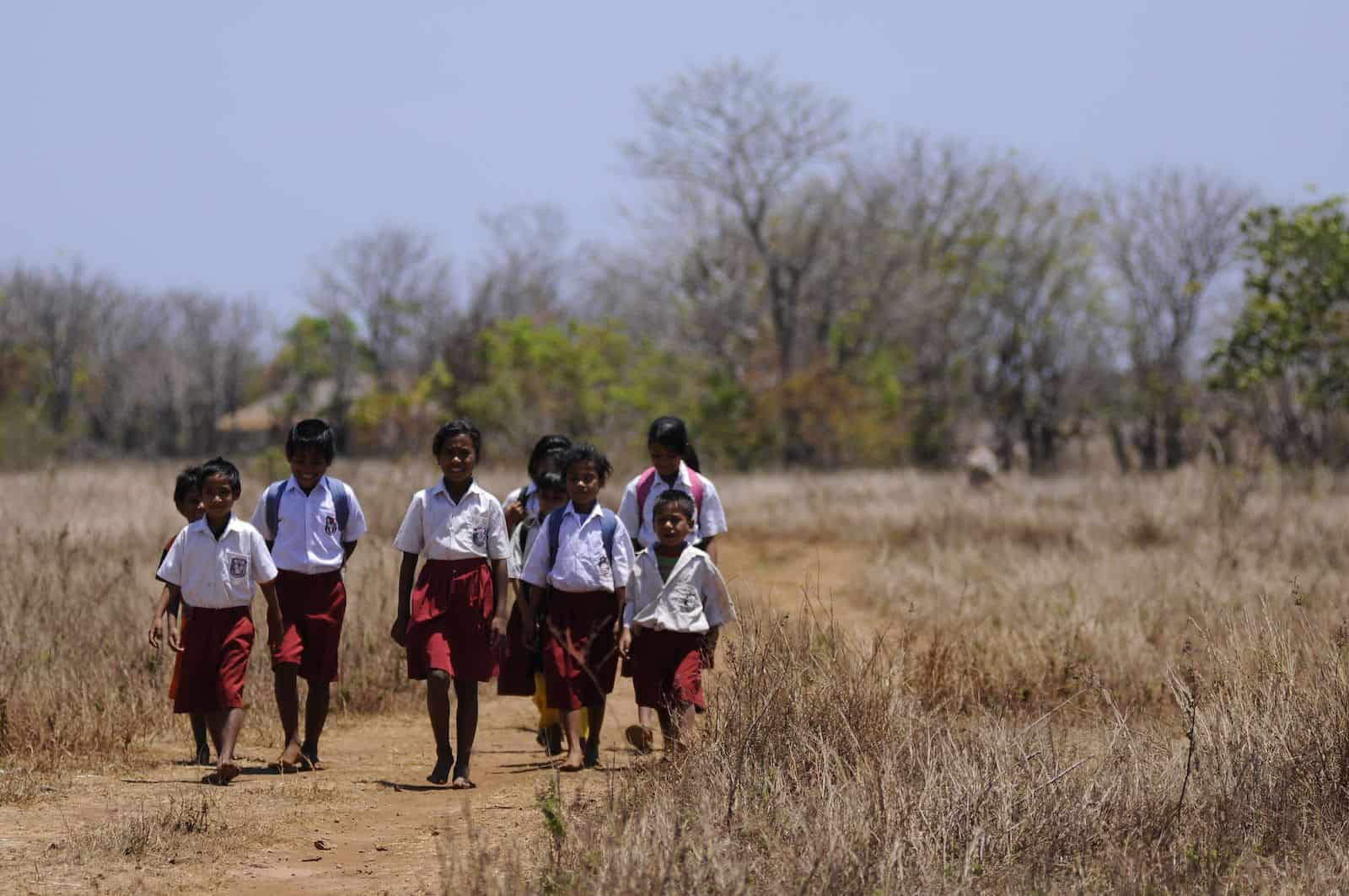 A group of students wearing red and white school uniforms walk down a dirt road in a brown field with trees in the background.