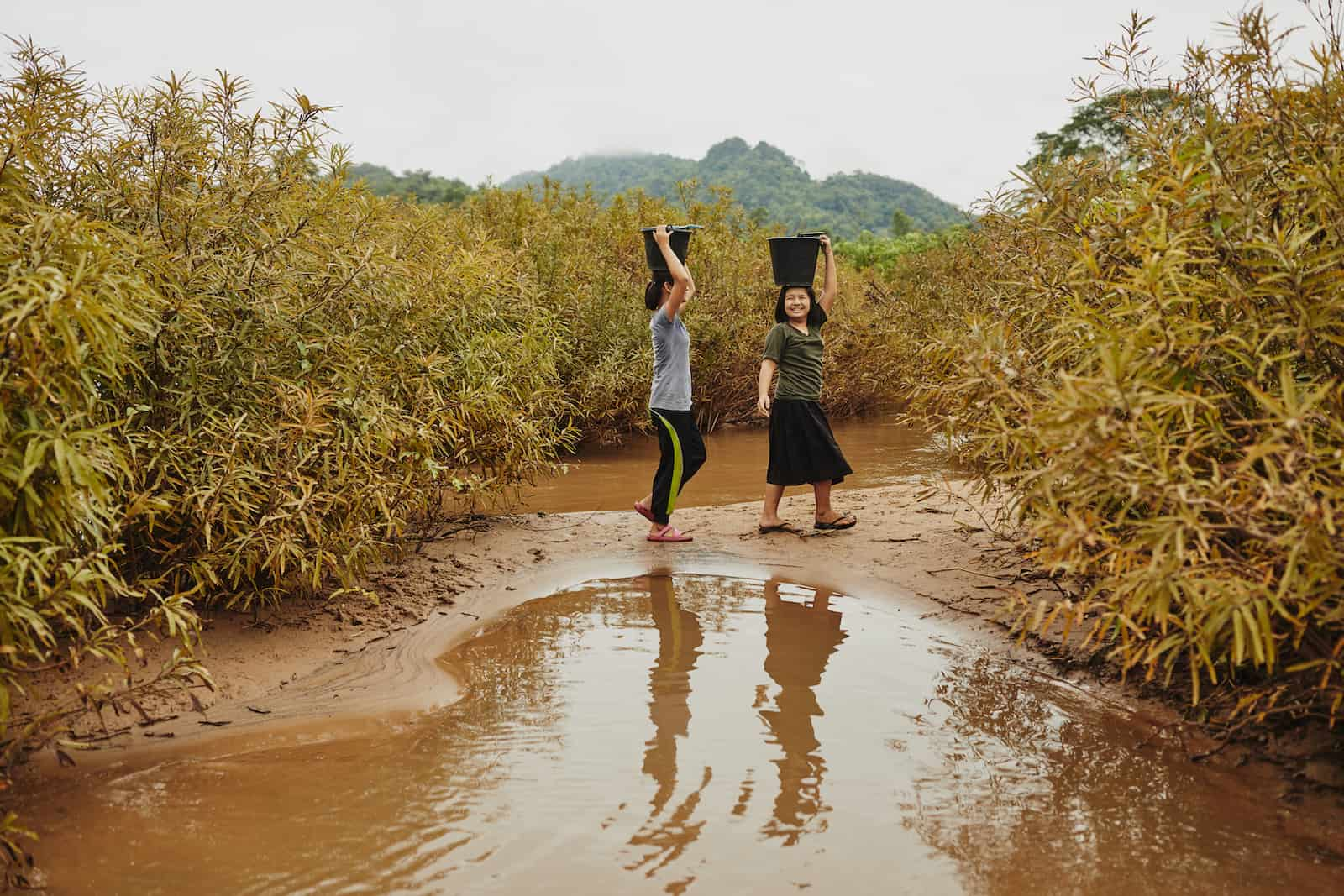 Two girls carry black buckets on their heads, standing in front of a small river, with foliage in the background.