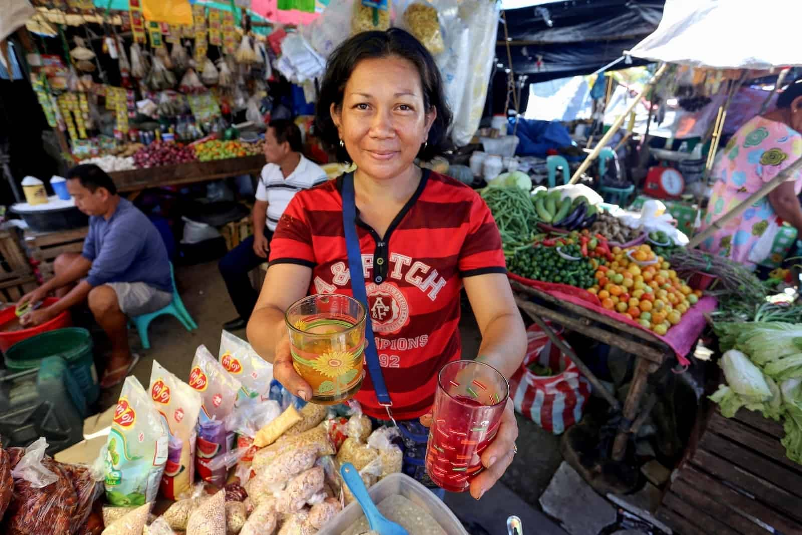A woman wearing a red shirt holds out two drinks, standing in a grocery stall.