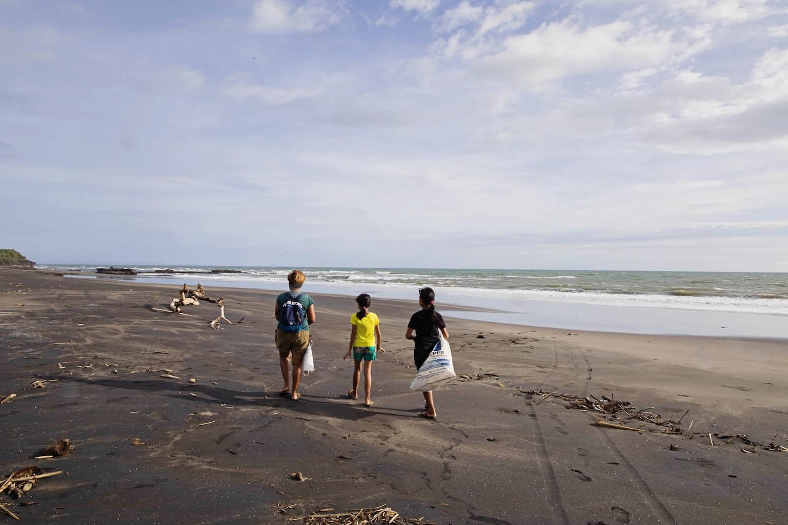 A woman walks down a wide beach with two children, holding bags in which they gather trash.
