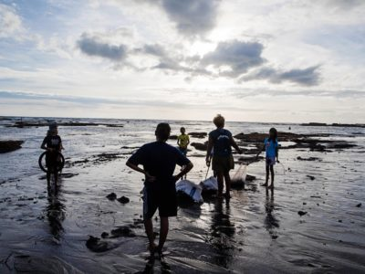 Two adults and three children stand on a beach on Bali at sunset, picking up trash.