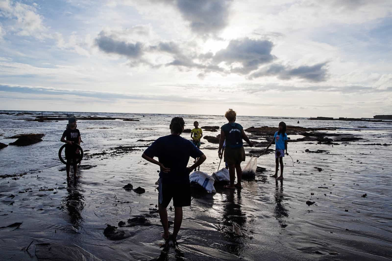 Two adults and three children who live in poverty stand on a beach on Bali at sunset, picking up trash to protect the environment.