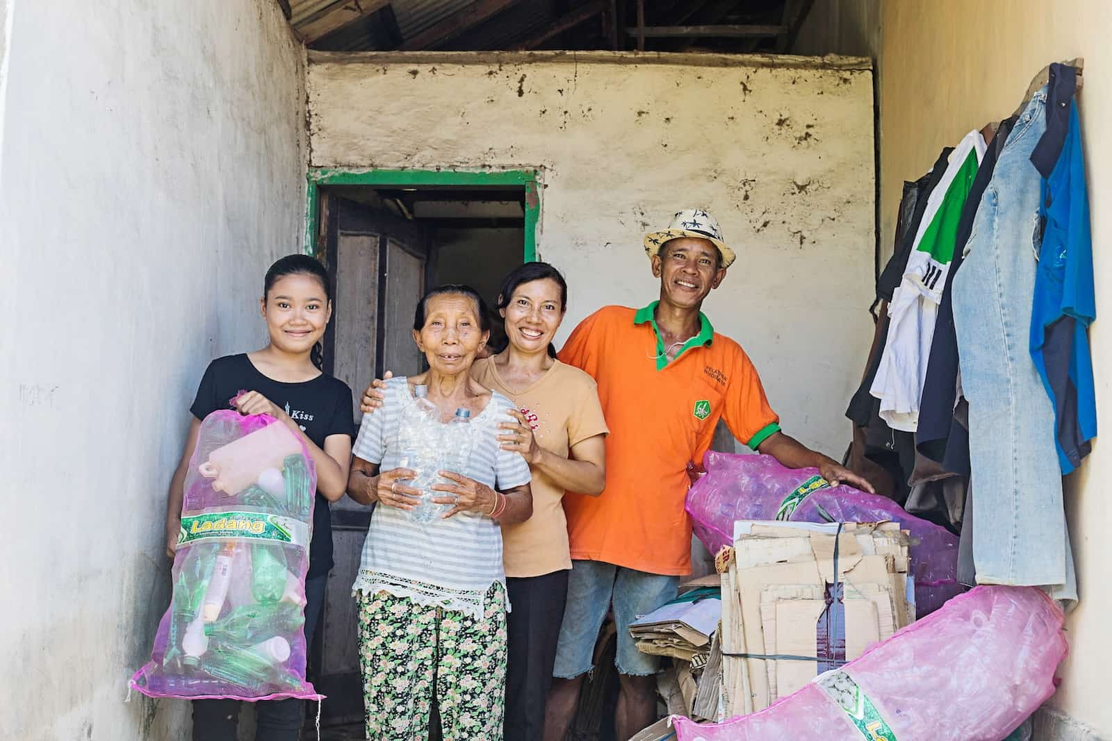 A family of a girl, grandmother, mother and father stand outside a home holding large bags full of plastic bottles.