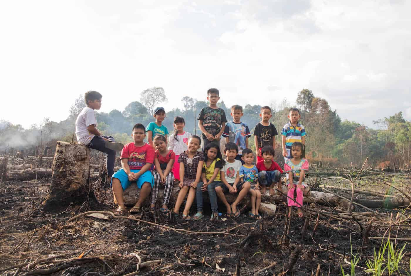 A group of children sit outside in a burned field. In the background is forest and smoke rising into the sky.
