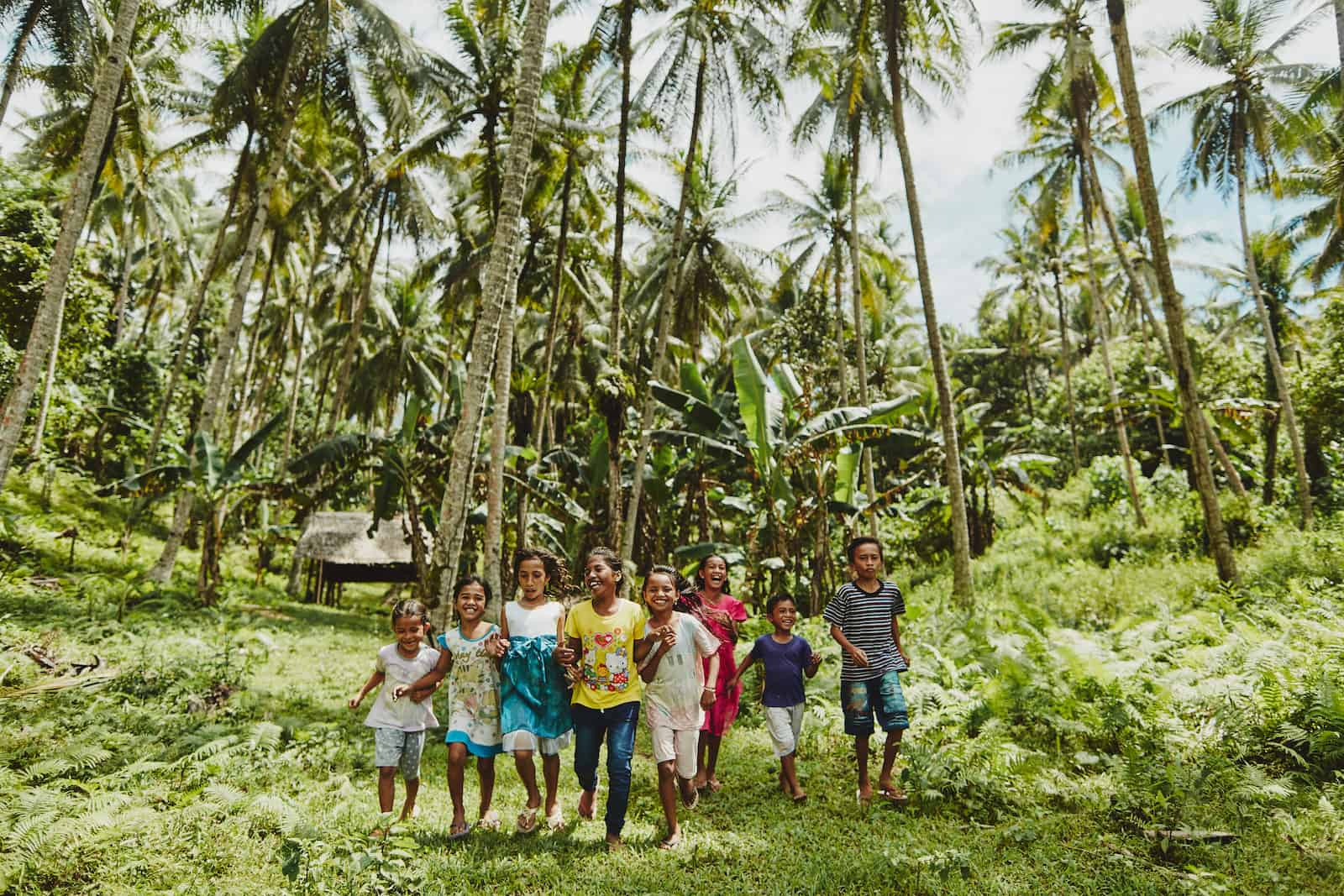 A group of children run through green grass in a forest of palm trees in Indonesia.