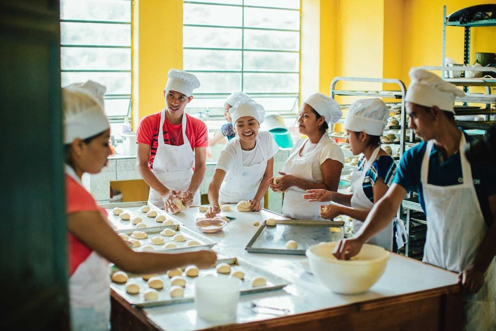 A group of students wear white aprons and chef's hats, standing around a large table, making rolls as they engage in vocational training in baking to defeat poverty.