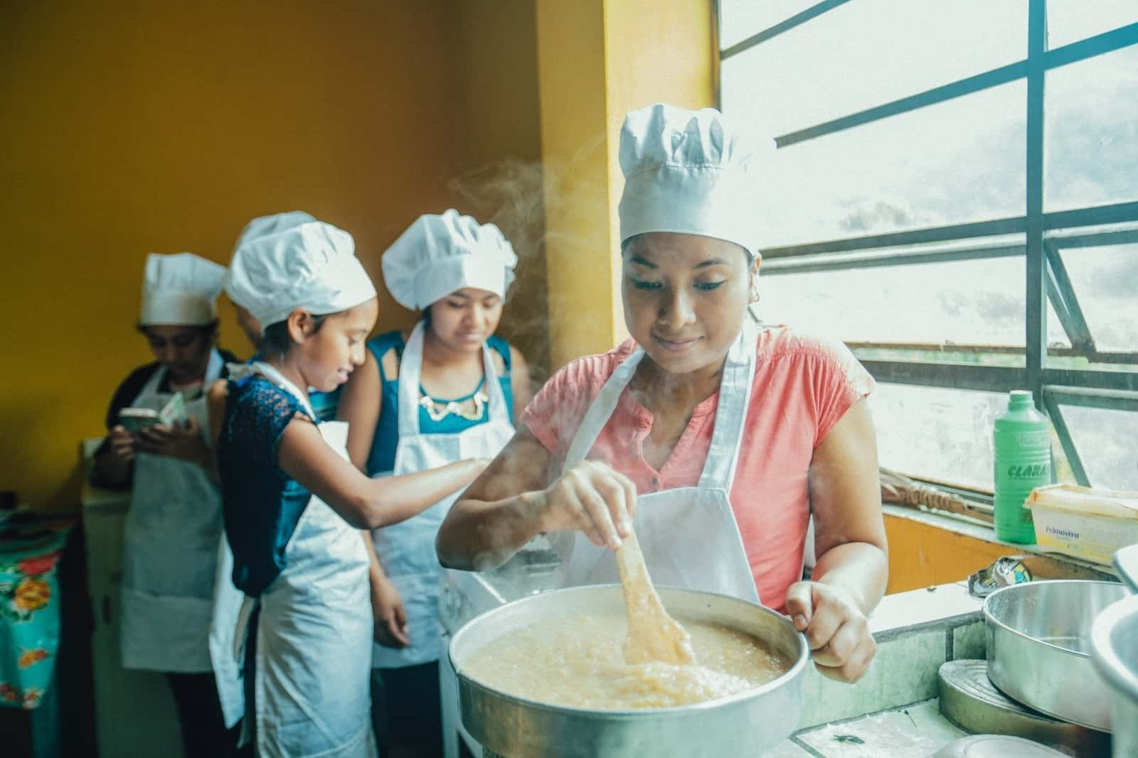 A young woman in a white apron and chef's hat stirs a large pot. Behind her, a group of girls focuses on a pan. They are doing vocational training in baking to escape poverty.