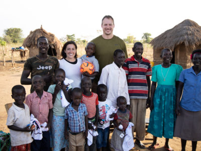 A group of people, Ugandans and two Americans, stand outside with grass thatched huts in the background, everyone smiling at the camera.